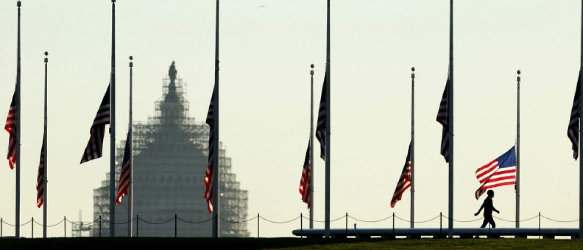 The dome of the U.S. Capitol is seen as a man walks past flags flying at half staff at the Washington Monument on the National Mall in Washington November 16, 2015. REUTERS/Kevin Lamarque/File Photo