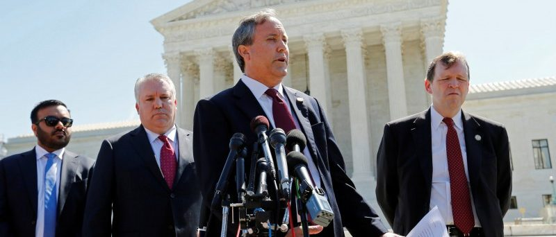 Texas Attorney General Ken Paxton (2nd R) holds a news conference to announce Texas and 20 other states have filed a lawsuit against the state of Delaware over millions of dollars in unclaimed official checks Paxton says have wrongly been remitted to Delaware, at the Supreme Court building in Washington, U.S. June 9, 2016. REUTERS/Jonathan Ernst