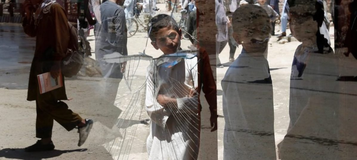 Afghan boys look a damaged window of a shop after a suicide attack in west of Kabul, Afghanistan May 25, 2016. REUTERS/Mohammad Ismail