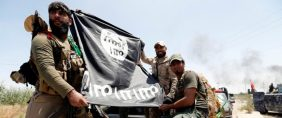 Shi'ite fighters hold an Islamic State flag which they pulled down as they celebrate victory in the town of Garma, Iraq. REUTERS/Thaier Al-Sudani