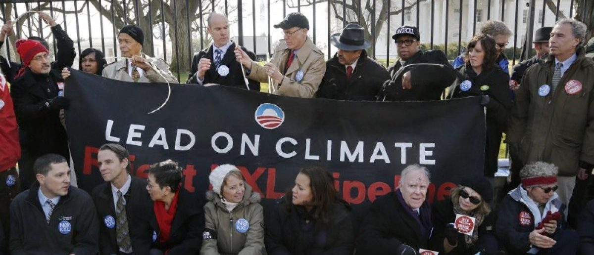 Civil rights activist Julian Bond (top row, 3rd L), Sierra Club Executive Director Michael Brune (top row, 4th L), and activists opposed to the Keystone XL tar sands pipeline project tie themselves to the White House fence during an environmental protest in Washington, DC, United States on February 13, 2013. REUTERS/Jonathan Ernst/File Photo