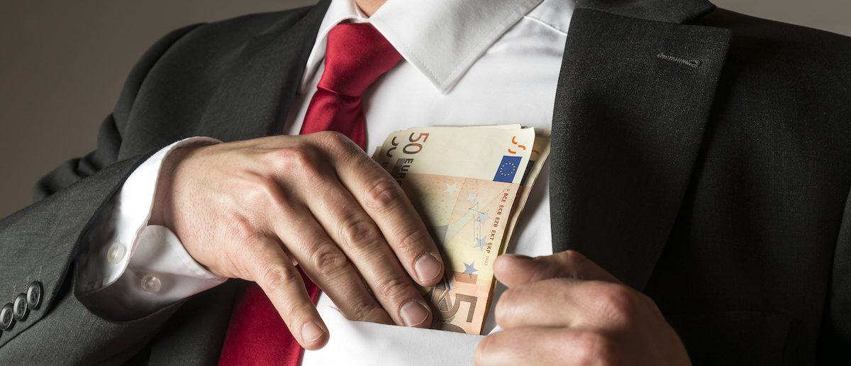 Businessman putting money in his shirt pocket (Credit: Shutterstock/Wolfgang Zwanzger)