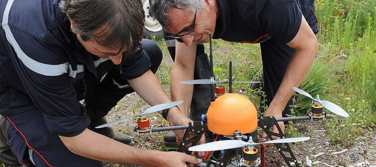 Two French firefighters prepare an Unmanned Aerial Vehicle (UAV) (aka drone) of French Fly-n-Sense (FNS) company before its take off, on July 12, 2012 near Mont-de-Marsan, southwestern France, during tests in the Landes forest region as an innovative forest surveillance system which will enable a real-time monitoring of fire outbreaks and the development of flames in French southwestern forests. ANDRIEU/AFP/GettyImages