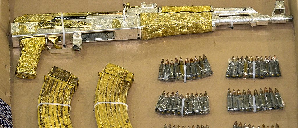 """A gold-plated AK-47 rifle seized to alleged leader of """"The Resistance"""" drugs cartel, Ramiro Pozos Gonzalez, aka """"El Molca"""", is presented to the press in Mexico City, on September 12, 2012. Pozos Gonzalez was arrested on the eve in the state of Mexico. AFP PHOTO/RONALDO SCHEMIDT        (Photo credit should read Ronaldo Schemidt/AFP/GettyImages)"""
