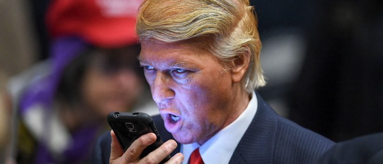 Donald Trump impersonator Robert S. Ensler speaks on a phone before a rally by Republican presidential hopeful Donald Trump at the Westgate Hotel and Resort in Las Vegas, Nevada on December 14, 2015. Trump will face off with Texas Sen. Ted Cruz, retired neurosurgeon Ben Carson and six other main stage candidates at the GOP debate on December 15. AFP PHOTO / ROBYN BECK / AFP / ROBYN BECK (Photo credit should read ROBYN BECK/AFP/Getty Images)