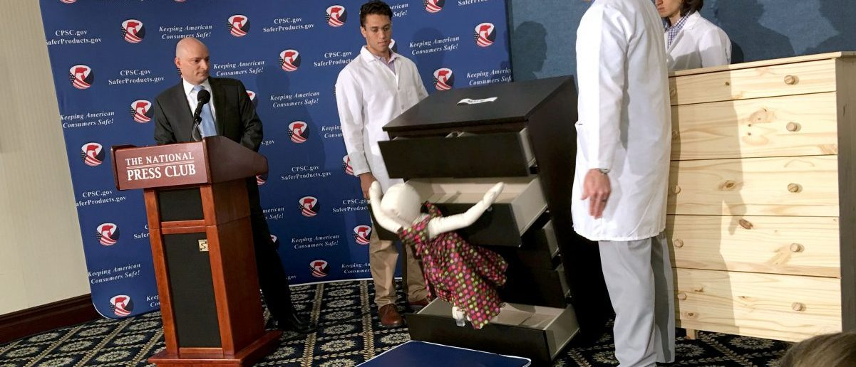 Elliot Kaye (L), chair of the Consumer Product Safety Commission (CPSC) and CPSC employees watch as a 28-pound (13 kilo) dummy(C) falls over and under IKEAs Malm model chest of drawers, during a live demonstration at the National Press Club in Washington, DC 28 June, 2016. / AFP / Carlos HAMANN (Photo credit should read CARLOS HAMANN/AFP/Getty Images)