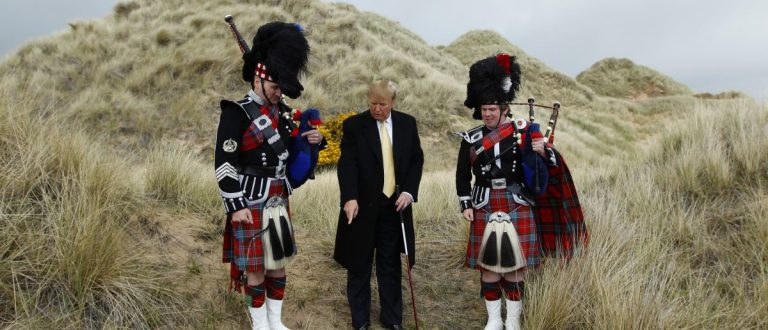 U.S. property mogul Donald Trump (C) poses next to bagpipers during a media event on the sand dunes of the Menie estate, the site for Trump's proposed golf resort, near Aberdeen, north east Scotland May 27, 2010. REUTERS/David Moir