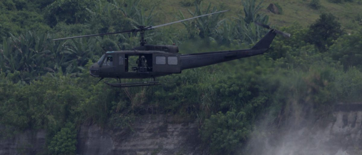 Huey helicopter hovers as U.S. marines patrol during Philippines-U.S.combine arms live fire exercise at Crow Valley in Tarlac city