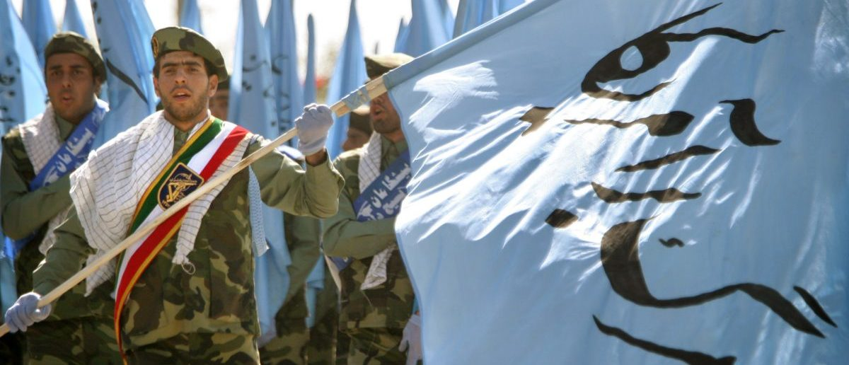 """Iranian revolutionary guard volunteers, with a banner reading """"Death to America"""", march during a military parade to commemorate the start of the 1980-88 Iran-Iraq war in Tehran, September 21, 2004. Iran is determined to press ahead with its nuclear programme even if it results in a halt of U.N. checks of the Islamic Republic's nuclear sites, President Mohammad Khatami says on Tuesday. REUTERS/Morteza Nikoubazl"""