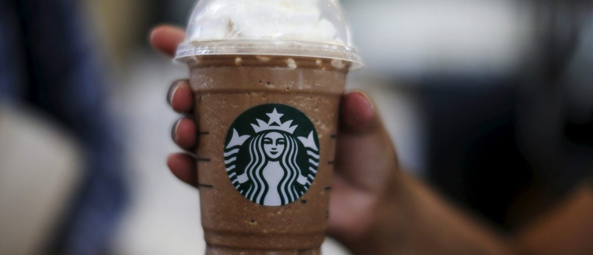 A woman holds a Frappuccino at a Starbucks (REUTERS/Lucy Nicholson)