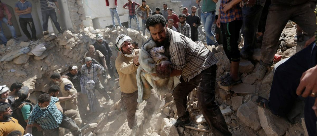 Civil defence members remove the body of a dead child from under the rubble at a site hit by airstrike in the rebel-controlled area of Maaret al-Numan town in Idlib province, Syria, June 12, 2016. REUTERS/Khalil Ashawi