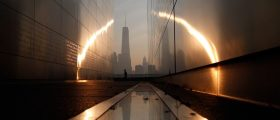 A man runs past the 9/11 Empty Sky memorial across from New York's Lower Manhattan and One World Trade Center in Liberty State Park in Jersey City