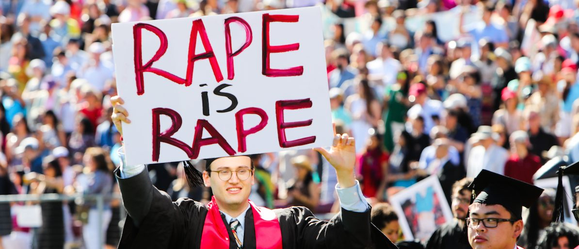 Stanford student Paul Harrison (C) carries a sign in a show of solidarity for a Stanford rape victim during graduation ceremonies at Stanford University, in Palo Alto, California, on June 12, 2016.  (GABRIELLE LURIE/AFP/Getty Images)