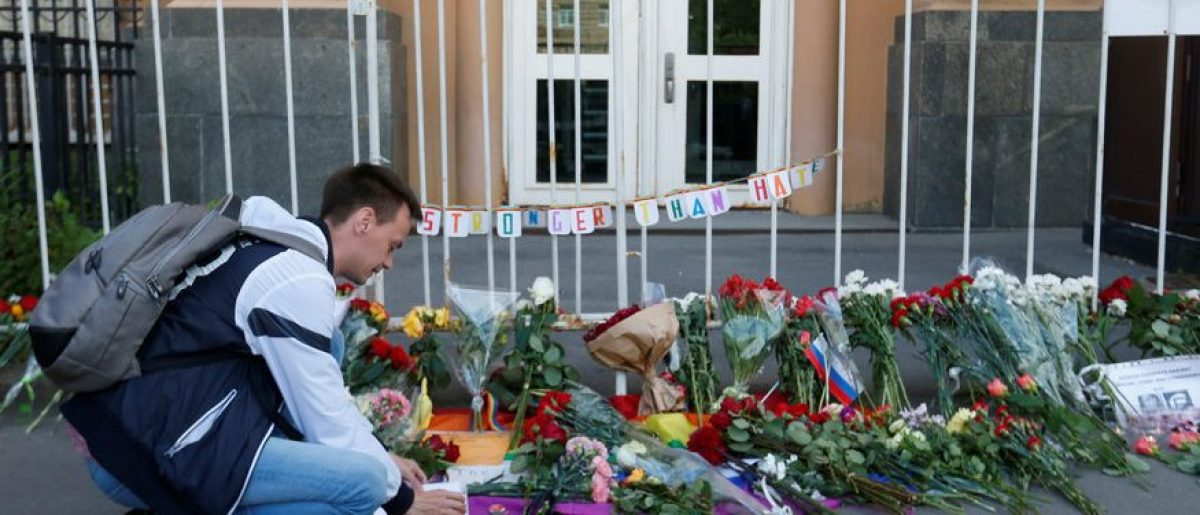 A man places a candle for the victims of the shooting at a gay nightclub in Orlando in front of the U.S. Embassy in Moscow, Russia, June 13, 2016. REUTERS/Maxim Zmeyev