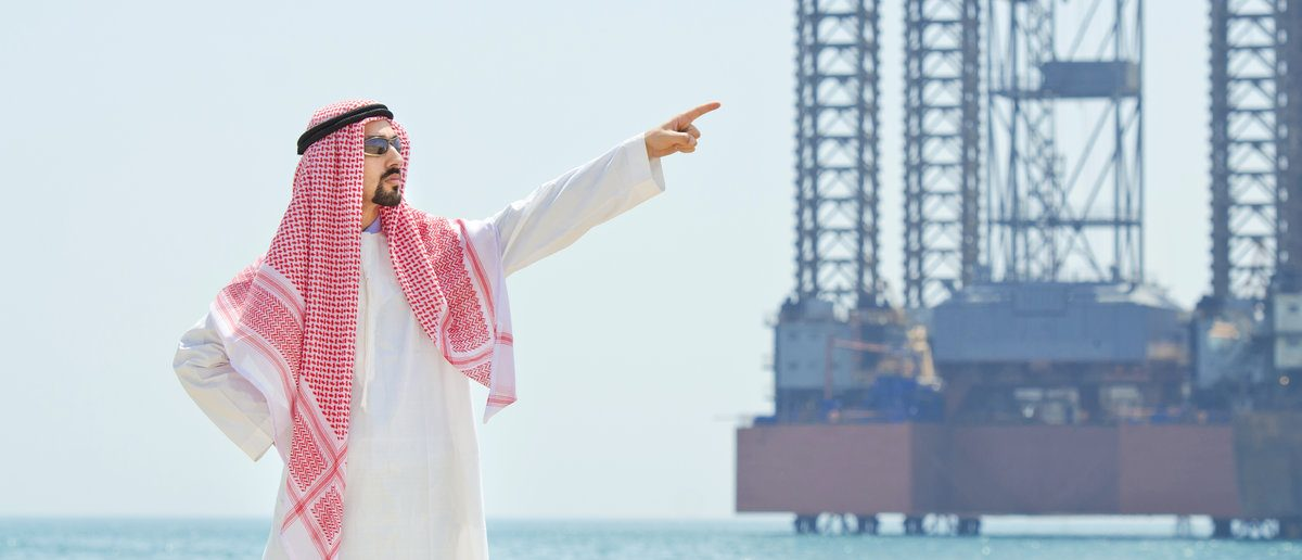 Arab on seaside near oil rig. (Shutterstock/Elnur)