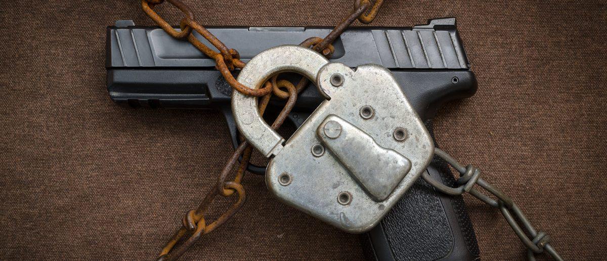 Gun Control Concept - Pistol behind Lock and Chain Christopher Slesarchik/Shutterstock.com