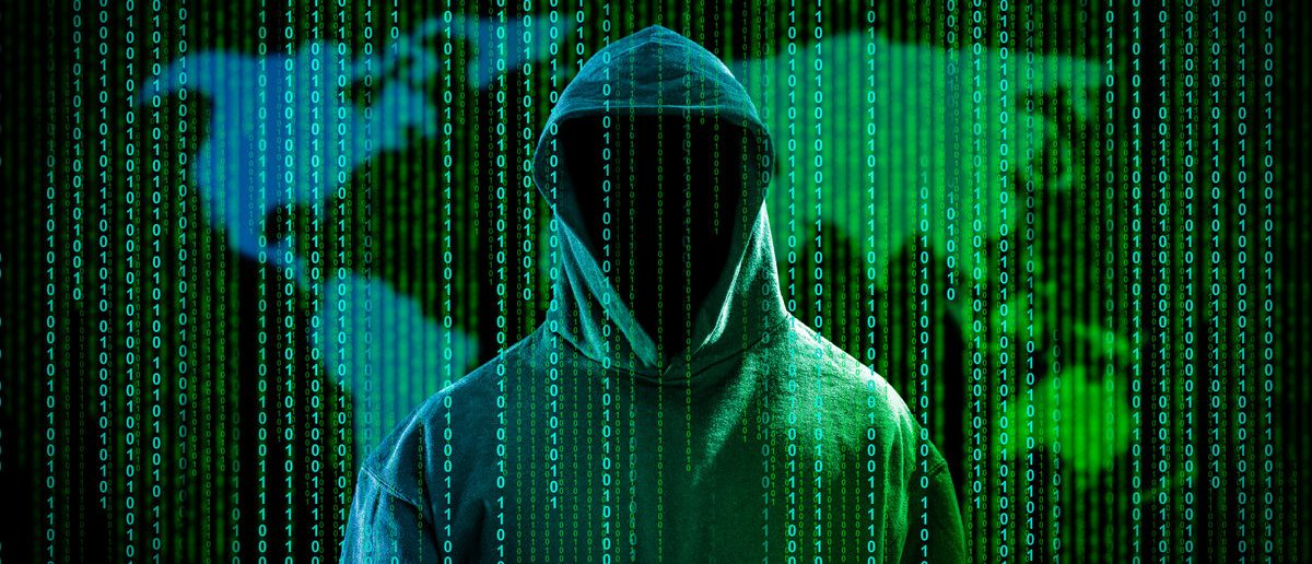 Hacker with a hood and binary code in front of world map. (Shutterstock/scyther5)