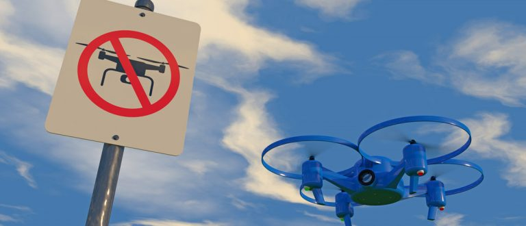 """3D illustration of UAV drone with """"No Drone Zone"""" graphic sign. Fictitious UAV, sign artwork, are unique designs. Depicting the restriction of drones. (Shutterstock.com/PixOne)"""
