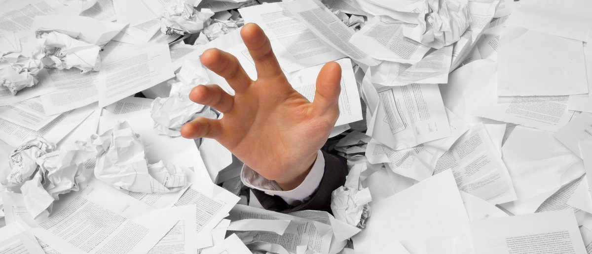 Hand reaches out from big heap of crumpled papers. (Shutterstock/Nomad_Soul)