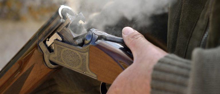 A smoking 12 bore shotgun having ejected spent a cartridge