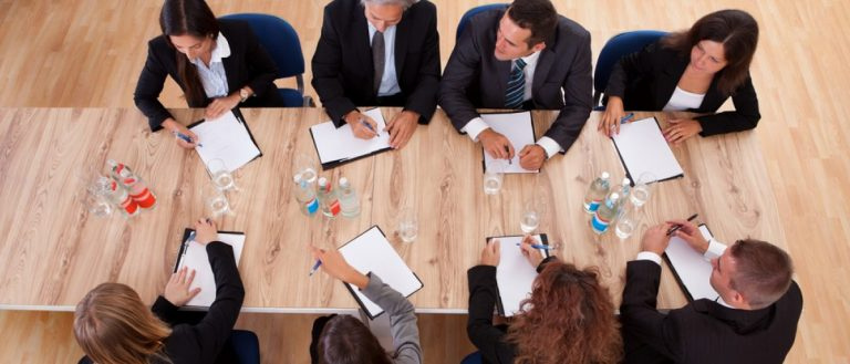 Overhead view of a board of trustees in a meeting seated around a wooden table with their notepads. [Shutterstock - Andrey_Popov]