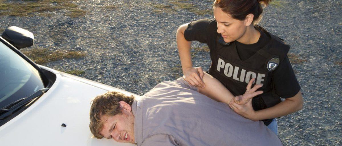 Police woman arresting man. Shutterstock - Rachel Donahue