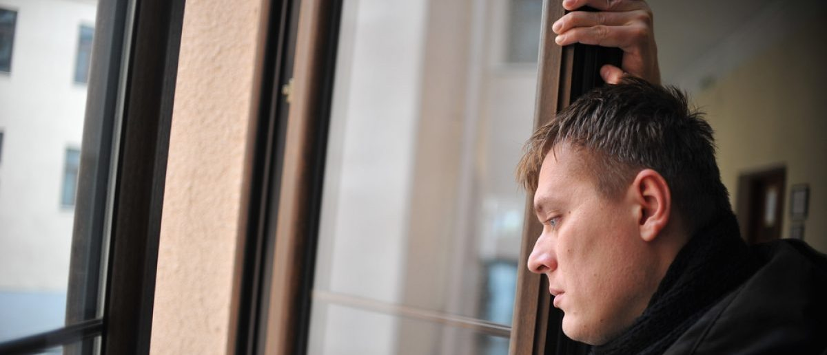Man looking out window after being fired. Shutterstock - Nevena Marjanovic 366904583)