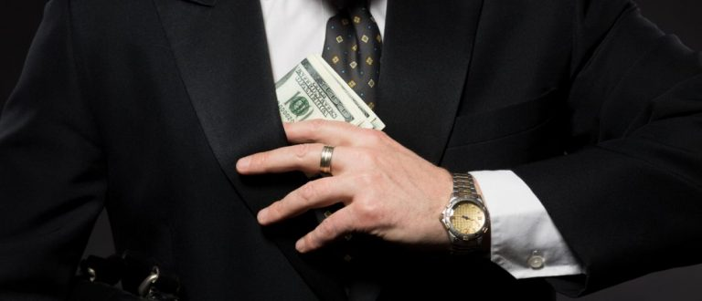 Businessman with money in studio. Currency bribing. Businessman hiding money in jacket pocket. Corruption and fraud concepts. (Credit: lipik/Shuttershock)