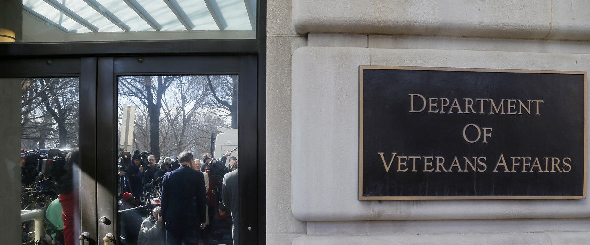 U.S. Department of Veterans Affairs Secretary Robert McDonald (reflected in doors, facing reporters) delivers an apology, for recent misstatements about his military record, to reporters outside VA headquarters in Washington, February 24, 2015. REUTERS/Jonathan Ernst