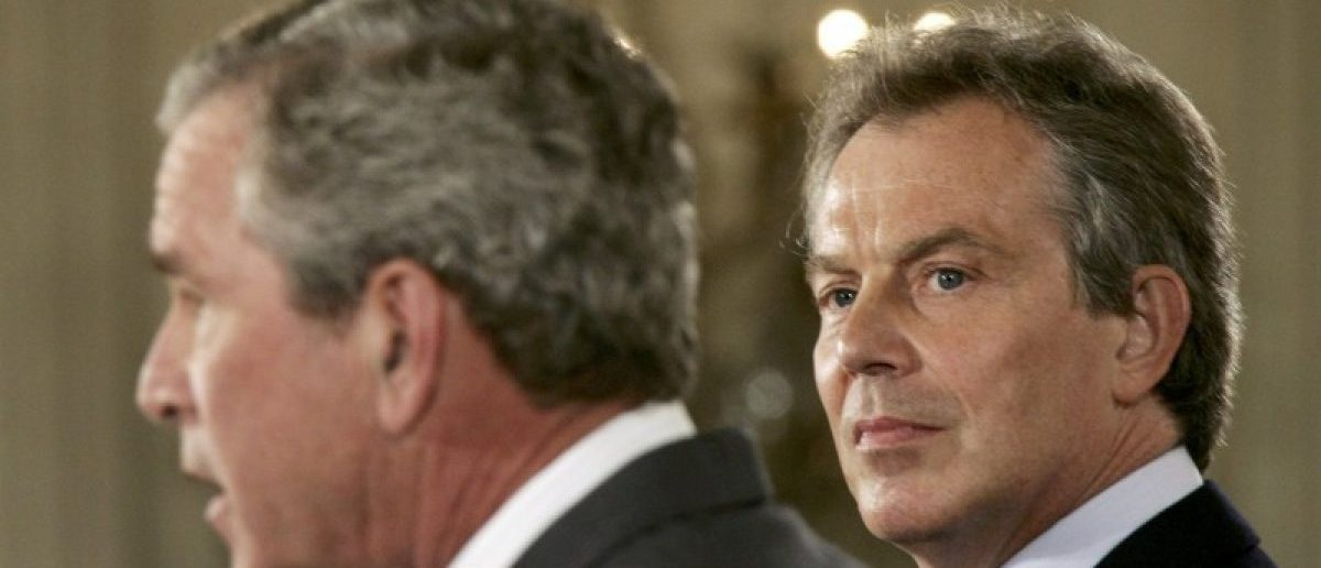 British Prime Minister Tony Blair (R) looks at U.S. President George W. Bush at a joint news conference in the East Room of the White House in Washington June 7, 2005. REUTERS/Jason Reed/File Photo