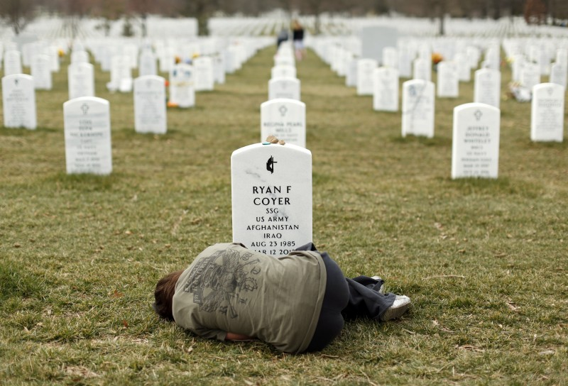 A woman lies down in front of the grave of her brother at Arlington National Cemetery near Washington