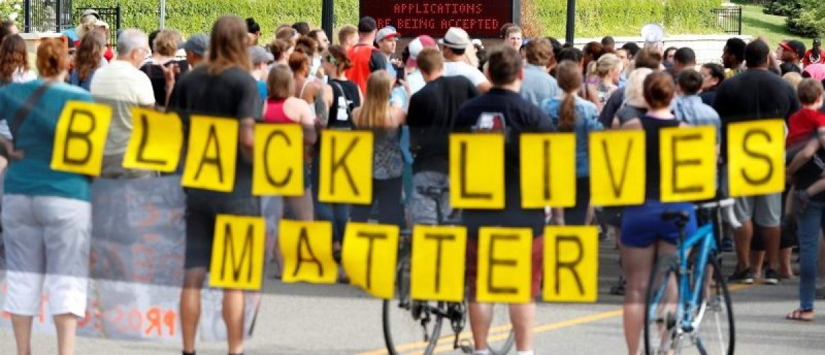 """Demonstrators carry a """"Black Lives Matter"""" banner and protest the shooting death of Philando Castile as they gather in front of the police department in St Anthony, Minnesota, U.S., July 10, 2016. REUTERS/Adam Bettcher"""