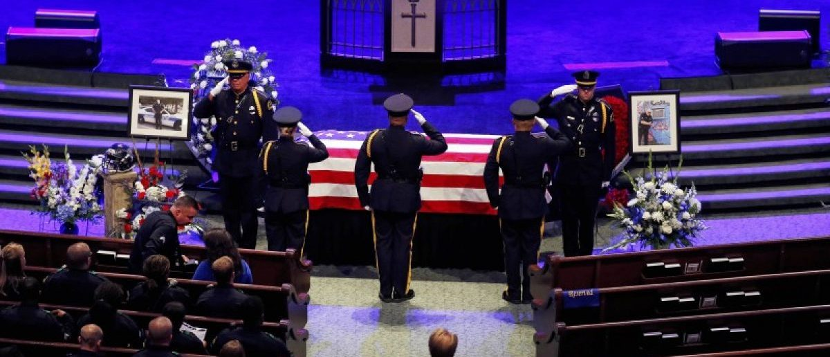 Police officers pay their respects ahead of the funeral for Officer Lorne Ahrens in Plano, Texas, U.S. July 13, 2016. Five officers, including Ahrens, were killed in a shooting incident in Dallas July 7. REUTERS/Carlo Allegri