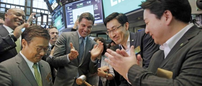 Japan's Line Corp. Chief Global Officer Jungho Shin (2nd L) rings the bell as CFO In Joon Hwang (R) and Chief Strategy and Marketing Officer Jun Masuda (L) look on along with NYSE president Tom Farley during the company's IPO on the floor of the New York Stock Exchange (NYSE) in New York City, New York, U.S. July 14, 2016. REUTERS/Brendan McDermid