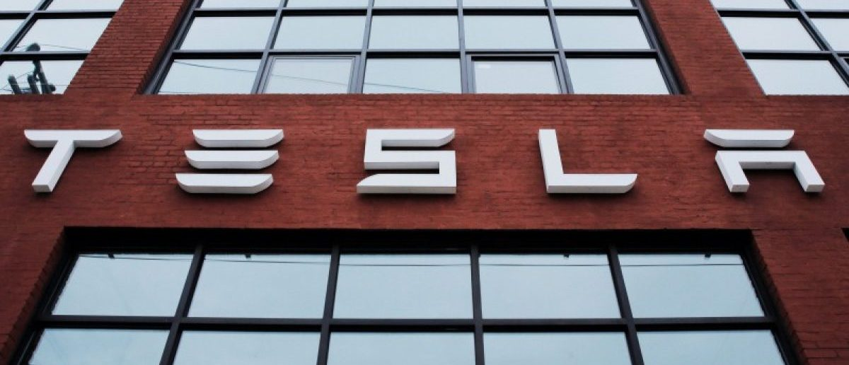 A Tesla logo hang on a building outside of a Tesla dealership in New York, U.S., April 29, 2016. REUTERS/Lucas Jackson