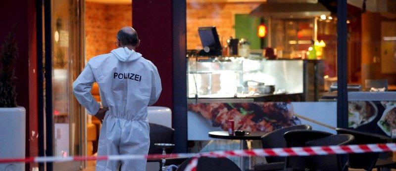 A police forensic expert works outside where a 21-year-old Syrian refugee killed a woman with a machete in Reutlingen