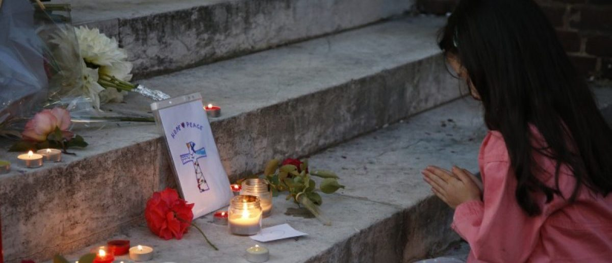 A young girl prays near flowers and candles at the town hall in Saint-Etienne-du-Rouvray, near Rouen in Normandy, France, to pay tribute to French priest, Father Jacques Hamel, who was killed with a knife and another hostage seriously wounded in an attack on a church that was carried out by assailants linked to Islamic State. REUTERS/Pascal Rossignol