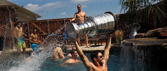 ALLEN, TEXAS, FRIDAY, AUGUST 31, 2012 -  LA Kings player Alec Martinez delivers the Stanley Cup poolside as he celebrates at his home with family and friends.  (Photo by Robert Gauthier/Los Angeles Times via Getty Images)