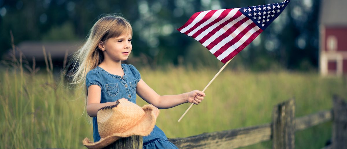 Little girl with American flag sitting on the fence