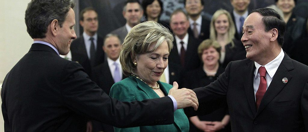 China's Vice Premier Wang Qishan and U.S. Treasury Secretary Timothy Geithner try to shake hands while U.S. Secretary of State Hillary Clinton stands in the middle ahead of the opening ceremony of the China-U.S. Strategic and Economic Dialogue May 24, 2010 in Beijing, China