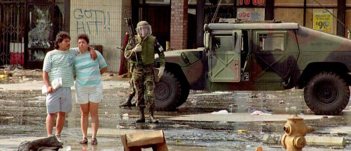 A member of the National Guard patrols the front of a Los Angeles shopping center 30 April 1992 as a couple embrace. The National Guard was brought in to control the rioting and looting. [Getty Images]