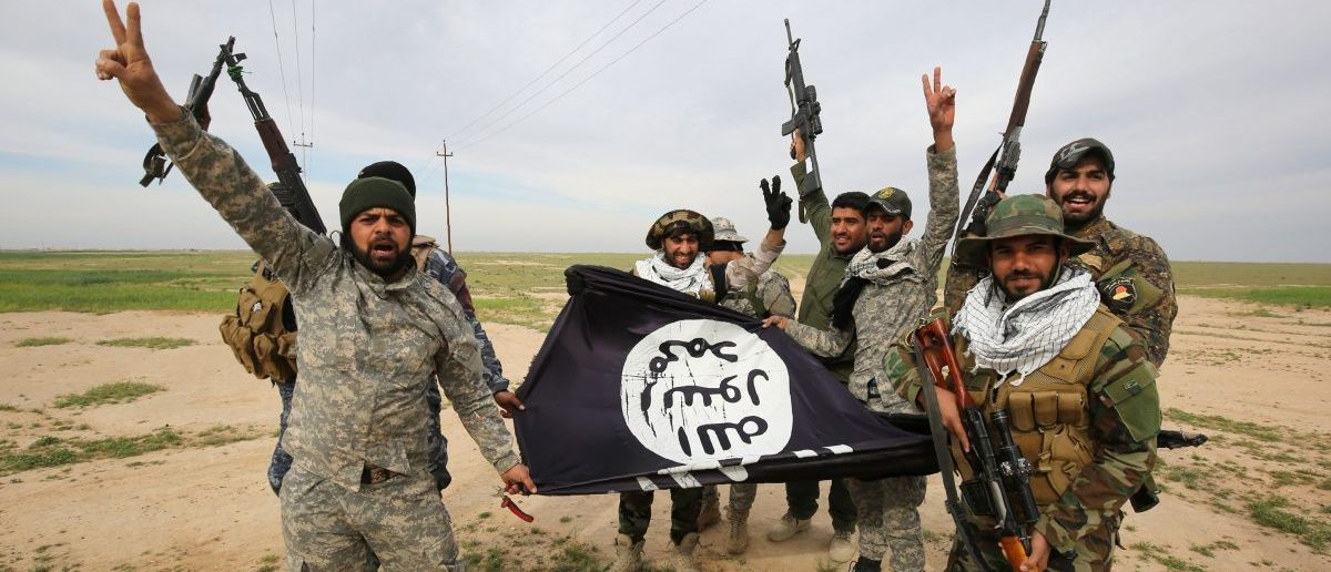 Iraqi Shiite fighters from the Popular Mobilisation units pose with a Islamic State (IS) group flag on March 3, 2016, during an operation in the desert of Samarra aimed at retaking areas from IS jihadists. Counter-terrorism forces, soldiers, police and allied paramilitaries are taking part in an operation launched on March 1, which is backed by artillery and both Iraqi and US-led coalition aircraft, aimed at retaking areas north of Baghdad, according to the Joint Operations Command. An Iraqi army colonel said that more than 7,000 security personnel would take part in the operation, which the operations command said aims to retake areas west of the city of Samarra. / AFP / AHMAD AL-RUBAYE