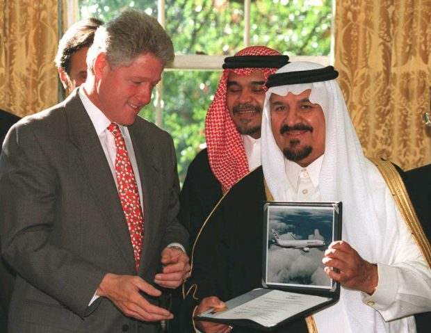 WASHINGTON, DC - OCTOBER 26: Saudi Defense and Aviation Minister Prince Sultan Bin Abdul Aziz(R) presents airplane contracts with US companies worth 6 billion USD to US President Bill Clinton(L) 26 October in the Oval Office at the White House in Washington DC. Prince Bandar(C) stands behind Clinton and Aziz. AFP PHOTO (Photo credit should read RICHARD ELLIS/AFP/Getty Images)