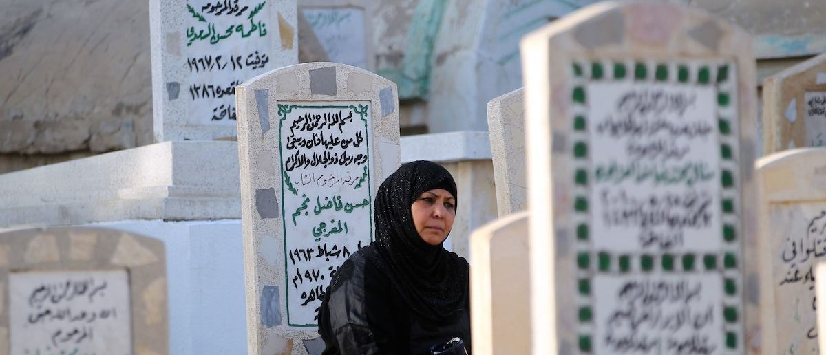 An Iraqi woman prays at the grave of a loved one at a cemetery in the capital Baghdad on July 6, 2016 on the first day of Eid al-Fitr holiday. AHMAD AL-RUBAYE/AFP/Getty Images