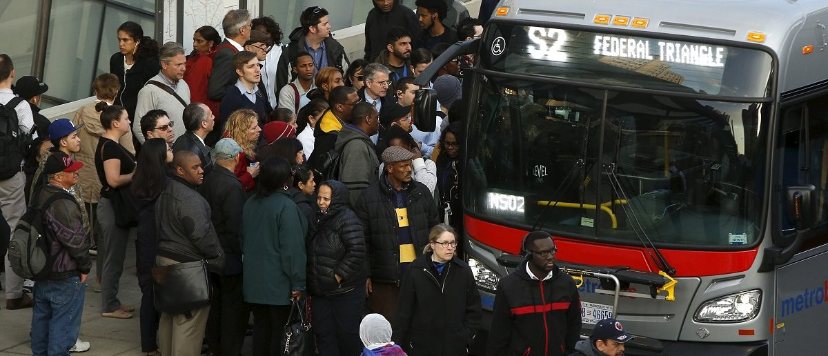 A long line of morning commuters board a bus for downtown Washington in Silver Spring, Maryland March 16, 2016. REUTERS/Gary Cameron