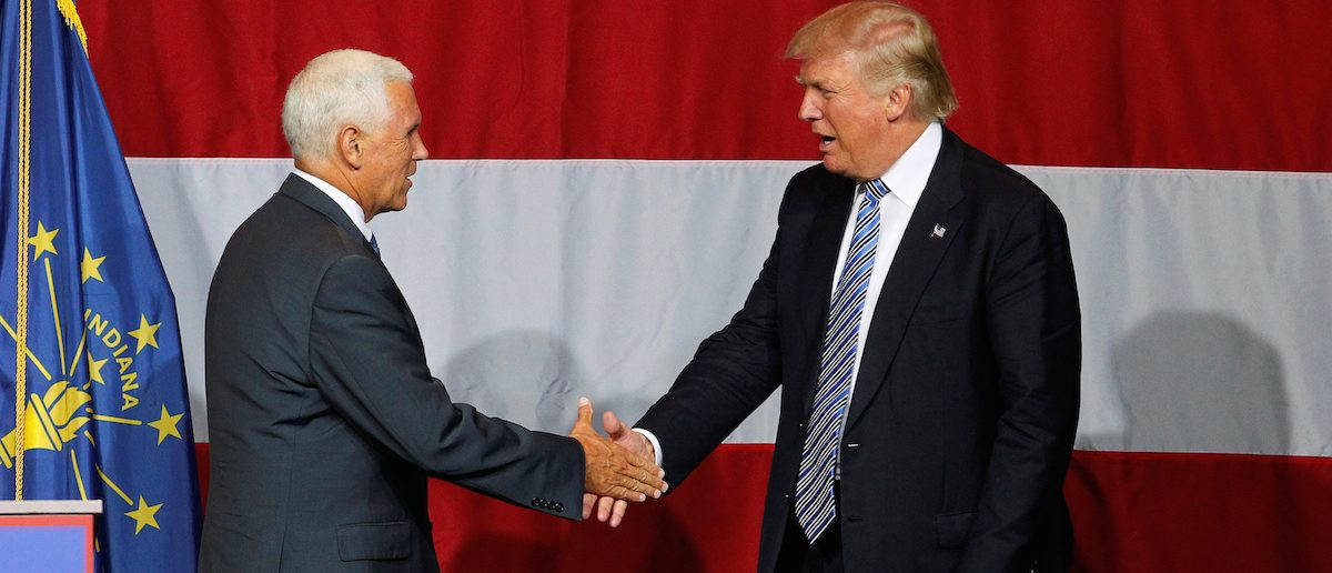 Republican presidential candidate Donald Trump shakes hands with Indiana Governor Mike Pence before addressing the crowd during a campaign stop at the Grand Park Events Center in Westfield, Indiana