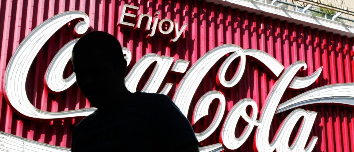 A pedestrian in Sydney passes a large Coca-Cola sign (REUTERS/Will Burgess)