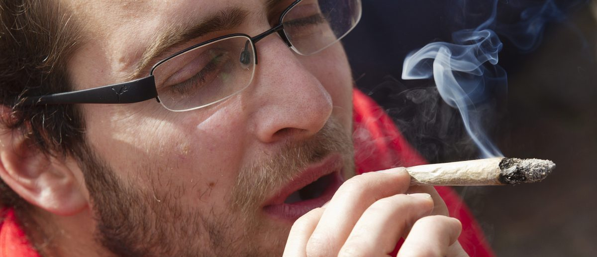A man lights up a joint during a protest march against a ban on selling cannabis to foreigners, in front of the town hall in Maastricht May 1, 2012. Tourists puffed on spliffs in the streets of southern Dutch cities and defiant coffee-shops sold joints to visitors in protest against the ban which took effect on Tuesday. REUTERS/Michael Kooren(NETHERLANDS