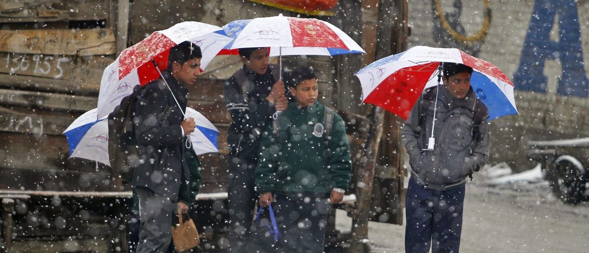 Schoolboys standing under umbrellas wait for a bus as snow falls in Srinagar March 16, 2015. Temperatures in Srinagar on Monday dipped to 0.6 degrees Celsius (33.08 degrees Fahrenheit), according to India's metrological department website. REUTERS/Danish Ismail