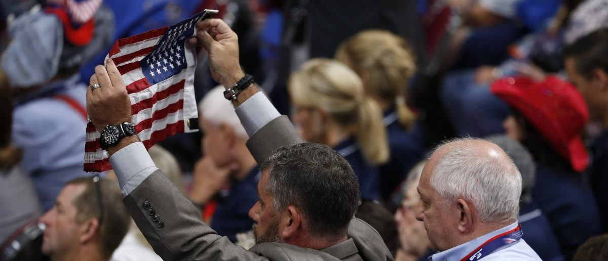 A delegate is assisted as he holds the American flag at the Republican National Convention (REUTERS/Mario Anzuoni)